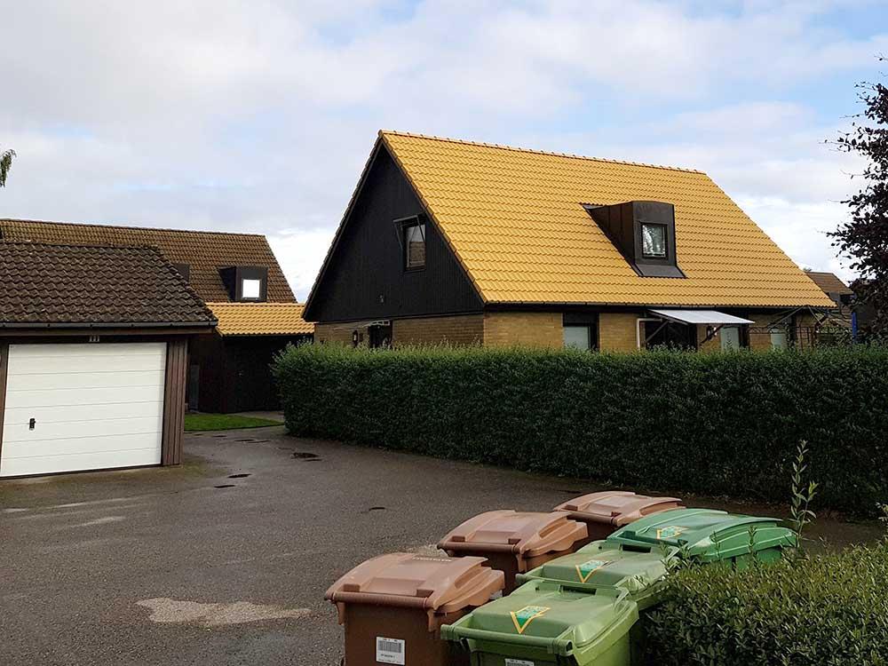 Takvård och takmålning på en villa med ett gult tak