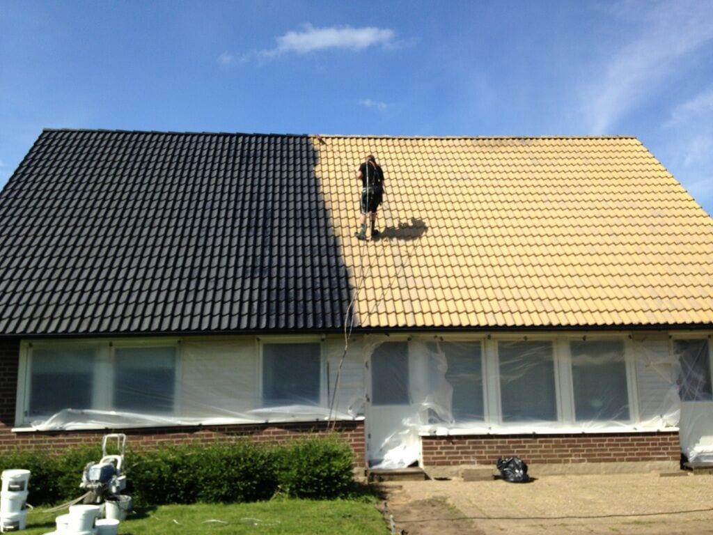 Pågående takmålning på ett gult tak