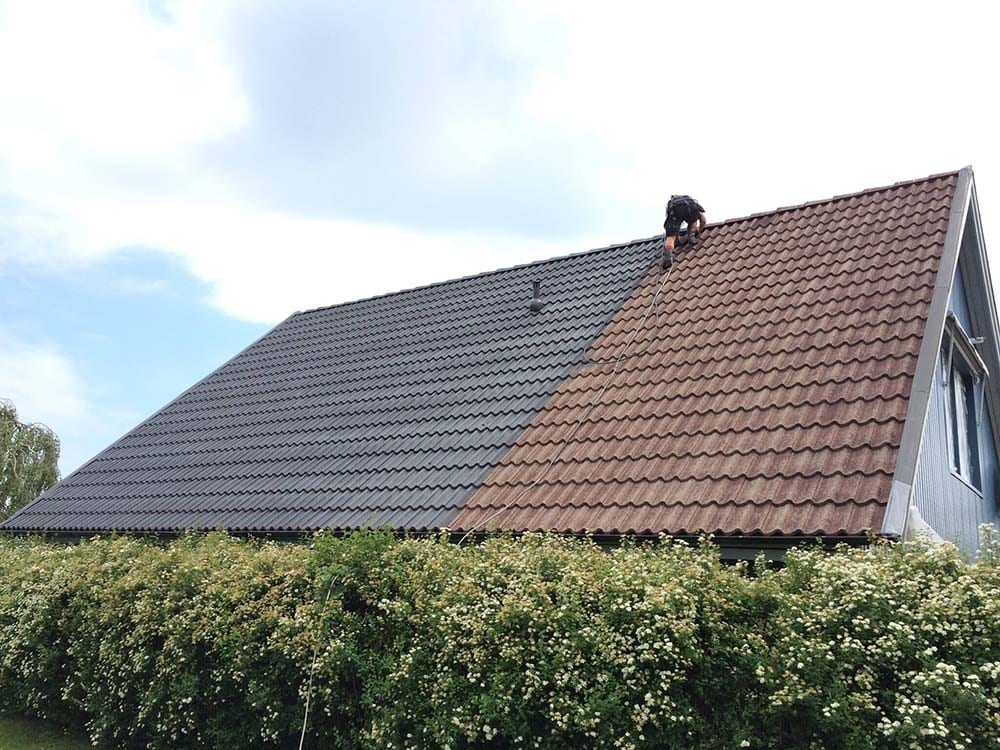 Hustvättarna hjälper till med att måla takpannor i betong.